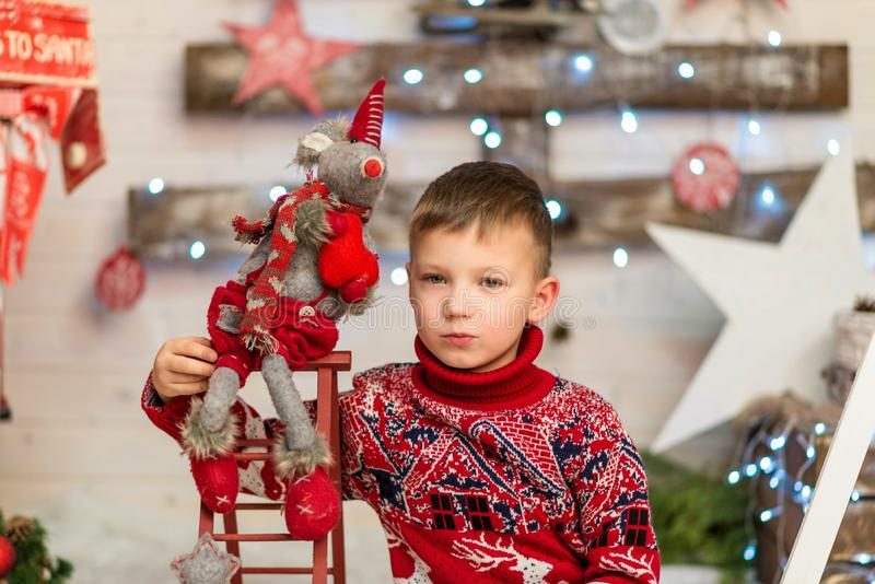 Boy in red Christmas sweater with soft toy mouse symbol of the year royalty free stock photography