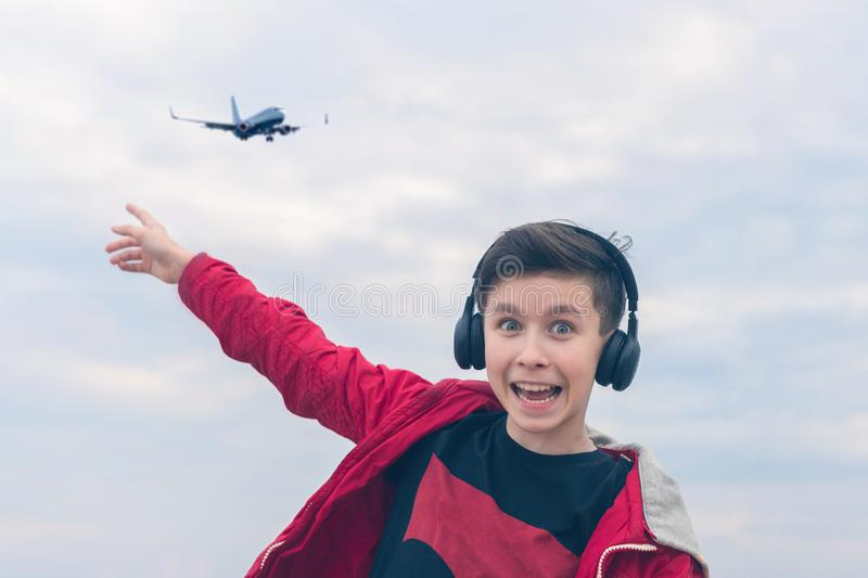 A boy in a red jacket and headphones smiling and shows his finger on the plane. Landing plane above sea waves in stormy weather. A boy in a red jacket and stock images