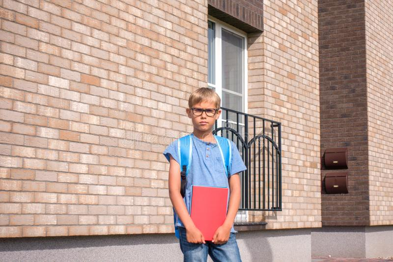 Boy with red notebook and backpack standing near residential apartment house. Kid ready to go to school.  stock photo