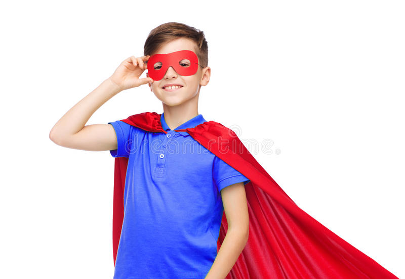 Boy in red super hero cape and mask. Carnival, childhood, power, gesture and people concept - happy boy in red super hero cape and mask stock images