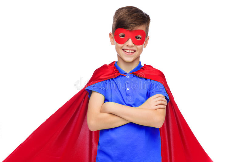 Boy in red super hero cape and mask. Carnival, childhood, power, gesture and people concept - happy boy in red super hero cape and mask royalty free stock photo