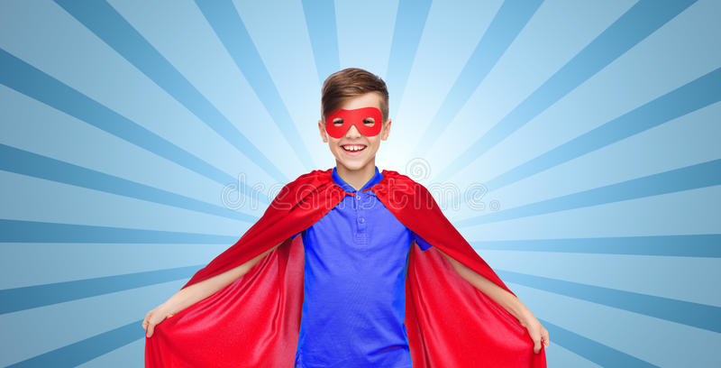 Boy in red super hero cape and mask. Carnival, childhood, power, gesture and people concept - happy boy in red super hero cape and mask over blue burst rays royalty free stock photo