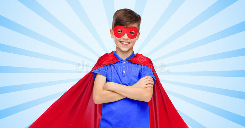 Boy in red super hero cape and mask. Carnival, childhood, power, gesture and people concept - happy boy in red super hero cape and mask over blue burst rays royalty free stock photography