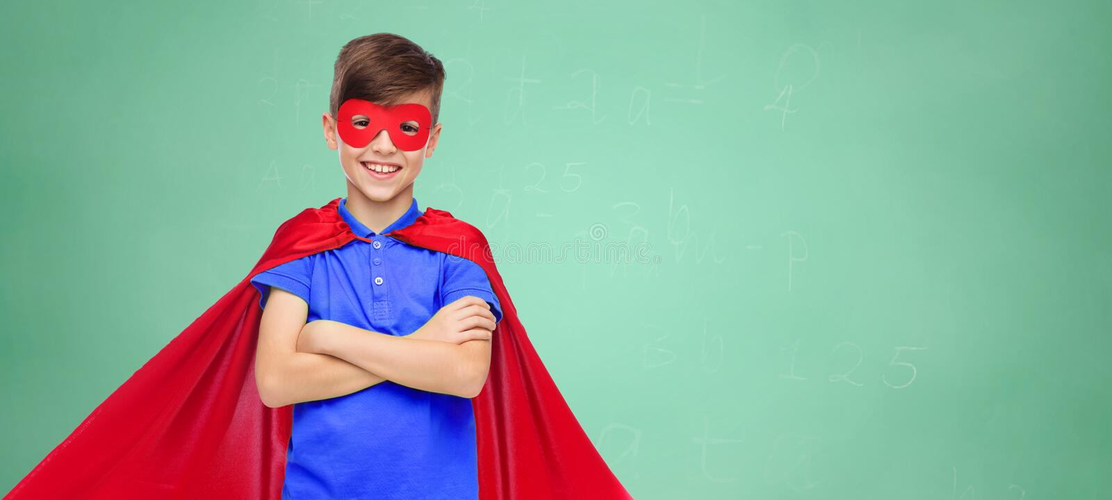 Boy in red super hero cape and mask. Education, childhood, power and people concept - happy boy in red super hero cape and mask over green school chalk board stock photo
