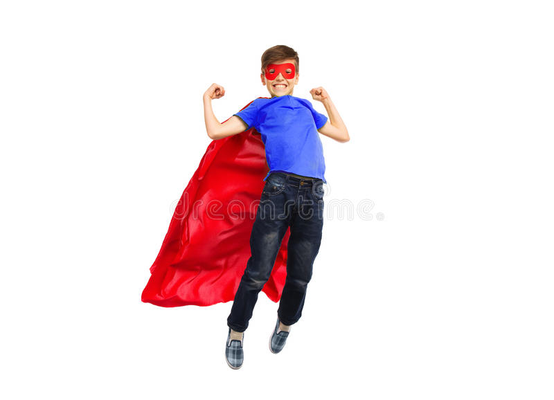Boy in red super hero cape and mask flying on air. Happiness, freedom, childhood, movement and people concept - boy in red super hero cape and mask flying in air stock images