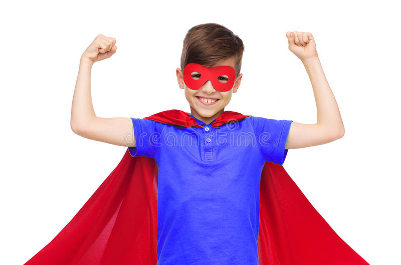 Boy in red super hero cape and mask showing fists. Carnival, childhood, power, gesture and people concept - happy boy in red super hero cape and mask showing stock image