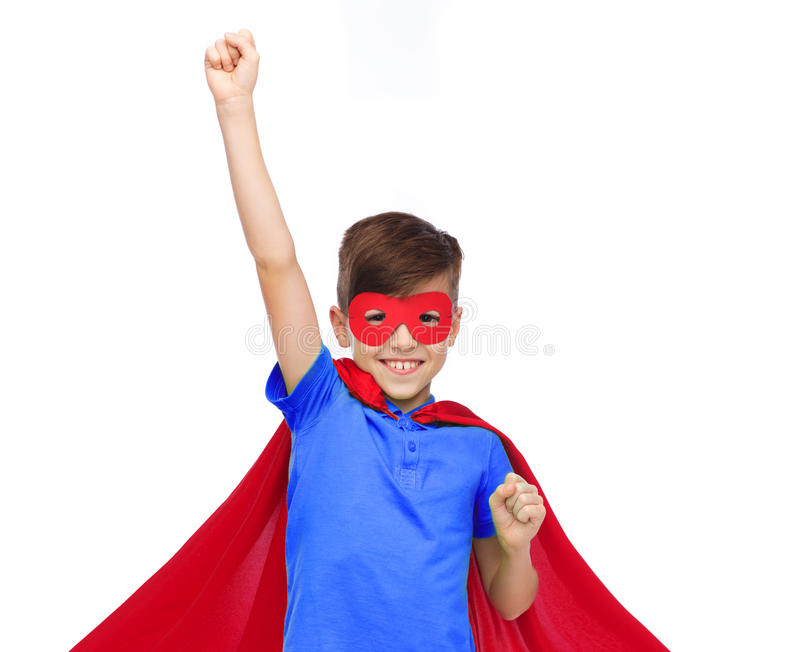 Boy in red super hero cape and mask showing fists. Carnival, childhood, power, gesture and people concept - happy boy in red super hero cape and mask showing stock photography
