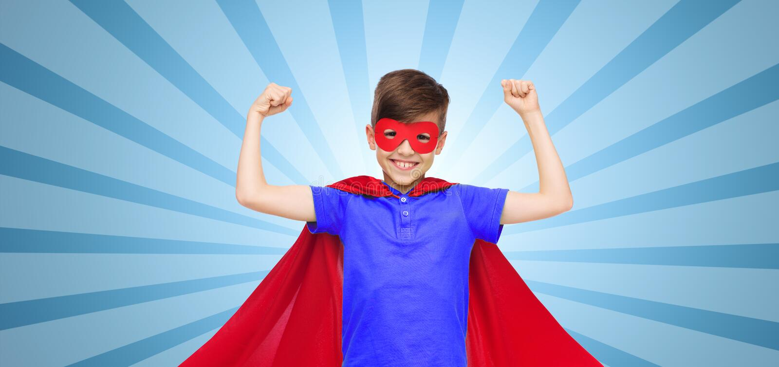 Boy in red super hero cape and mask showing fists. Carnival, childhood, power, gesture and people concept - happy boy in red super hero cape and mask showing royalty free stock image
