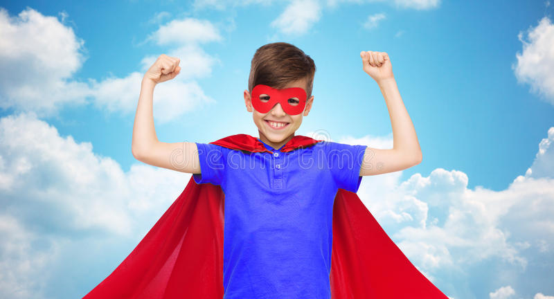 Boy in red super hero cape and mask showing fists. Carnival, childhood, power, gesture and people concept - happy boy in red super hero cape and mask showing stock images