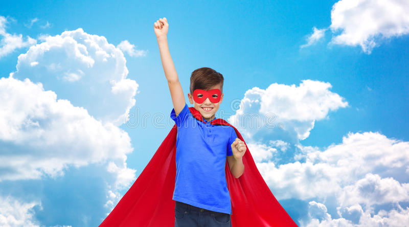 Boy in red super hero cape and mask showing fists. Carnival, childhood, power, gesture and people concept - happy boy in red super hero cape and mask showing stock photo