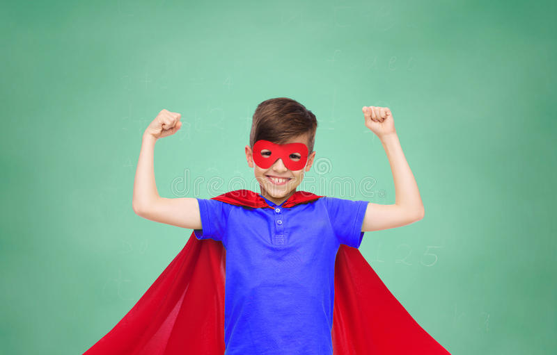 Boy in red super hero cape and mask showing fists. School, education, childhood, power and people concept - happy boy in red super hero cape and mask showing royalty free stock image