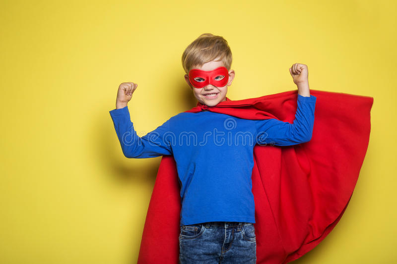 Boy in red super hero cape and mask. Superman. Studio portrait over yellow background. Boy in red super hero cape and mask. Studio portrait over yellow stock images