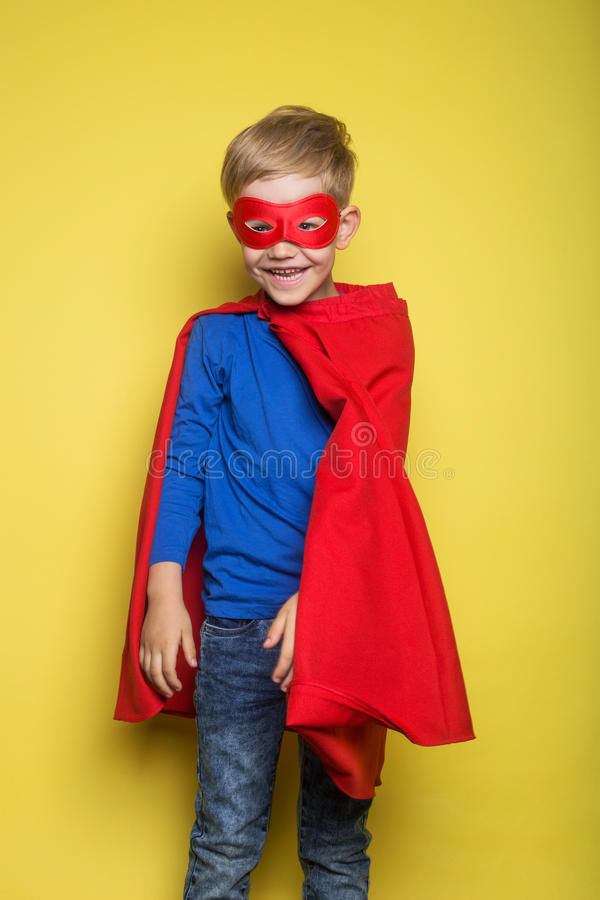 Boy in red super hero cape and mask. Superman. Studio portrait over yellow background. Boy in red super hero cape and mask. Studio portrait over yellow royalty free stock photography
