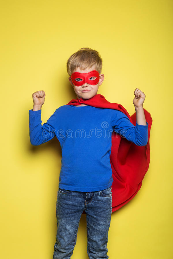 Boy in red super hero cape and mask. Superman. Studio portrait over yellow background. Boy in red super hero cape and mask. Studio portrait over yellow royalty free stock photos