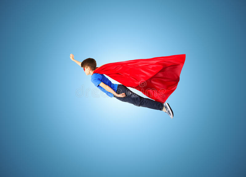 Boy in red superhero cape and mask flying on air royalty free stock images