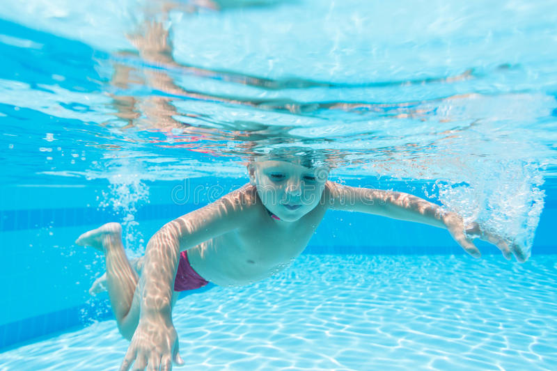 Boy in red swim trunks under water. In the pool stock images