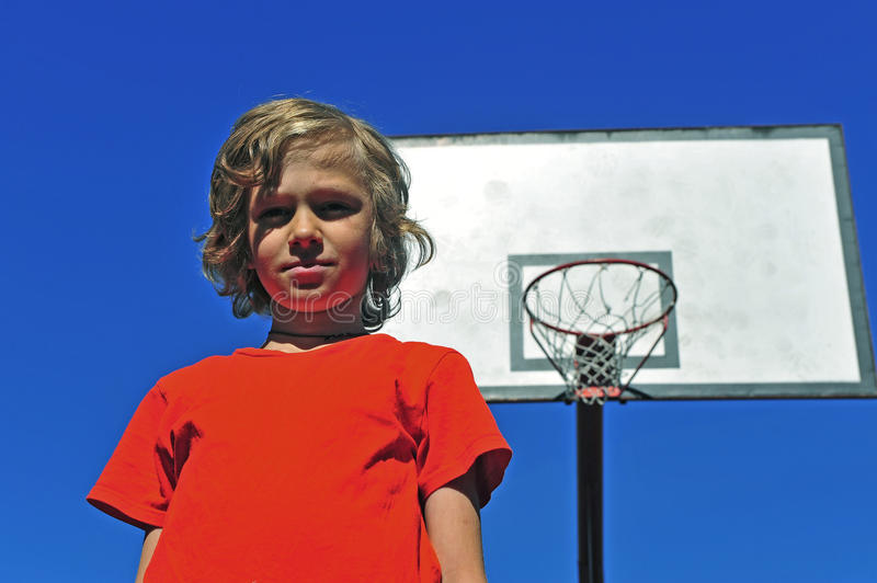 Boy in red t-shirt with basketball hoop on background. Boy in red t-shirt with the basketball hoop on background royalty free stock photo