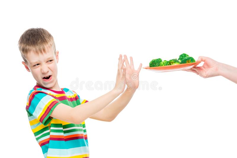 Boy refuses plate of broccoli for lunch, portrait is isolated on white. Background royalty free stock photos