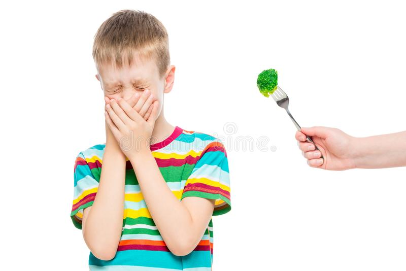 Boy refuses serving healthy broccoli, emotional portrait of a child isolated on white. Background stock photography