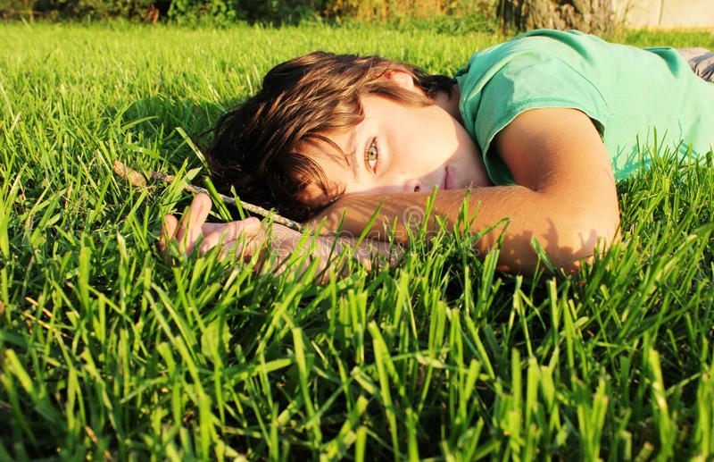 Boy relaxing on grass stock photo