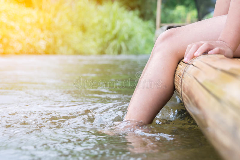 Boy relaxing and sitting on bamboo raft at river royalty free stock photography