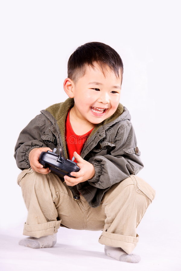 Boy with remote controller. A picture of a little chinese boy playing happily with a remote controller, laughing royalty free stock photography