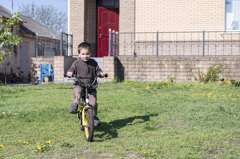 a boy rides his bike on a hot summer day. Boy riding a bicycle in the yard on a background of a brick house royalty free stock photography
