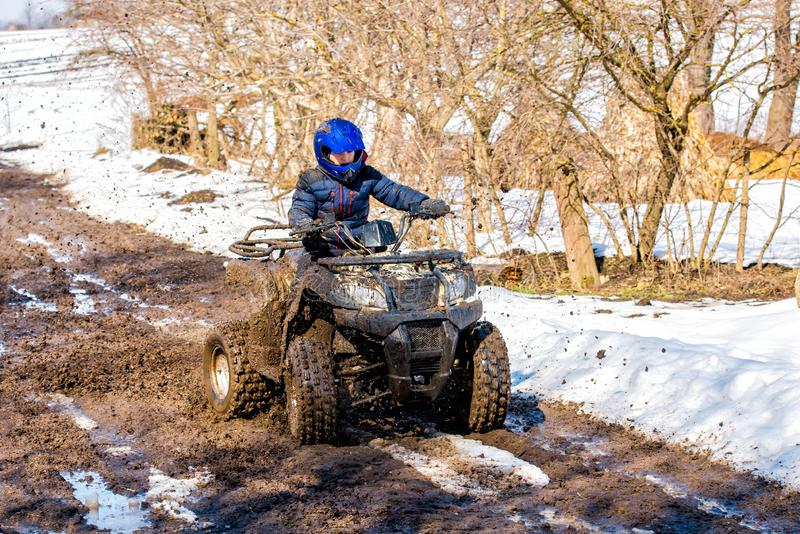 The boy is riding an ATV off-road stock photo