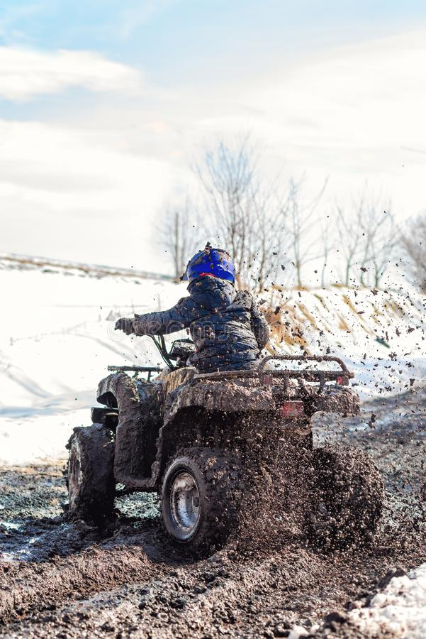 The boy is riding an ATV off-road stock images