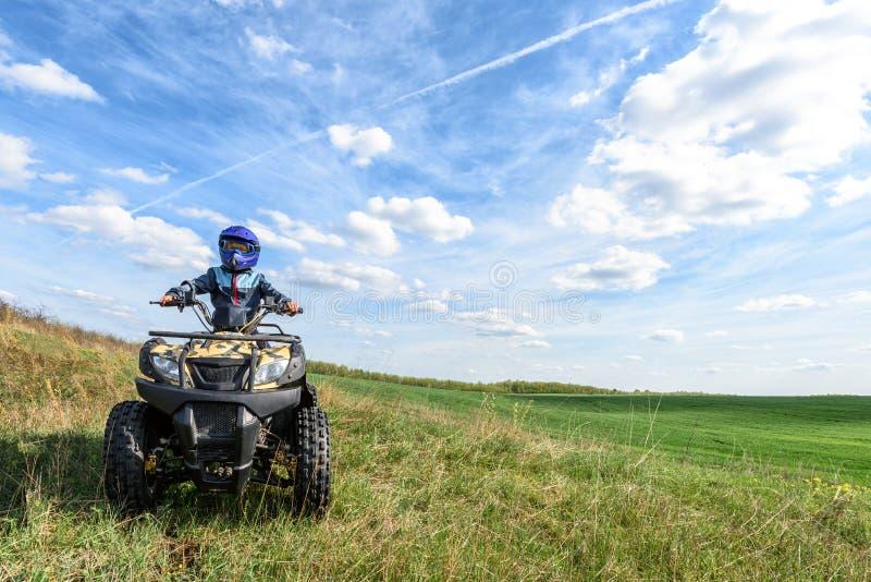The boy is riding an ATV off-road stock photos