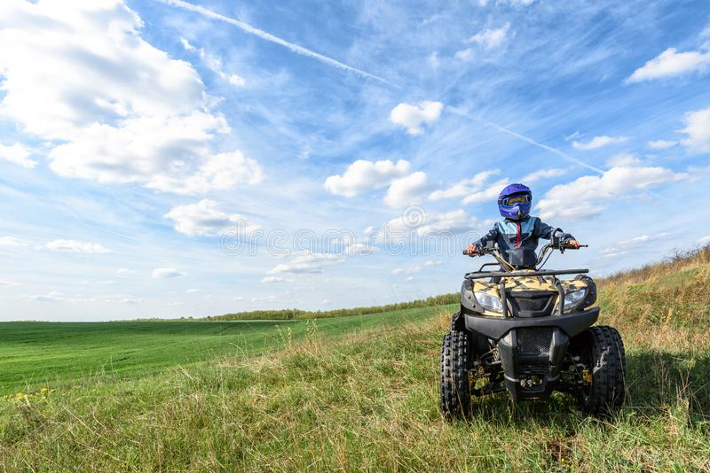 The boy is riding an ATV off-road stock photography
