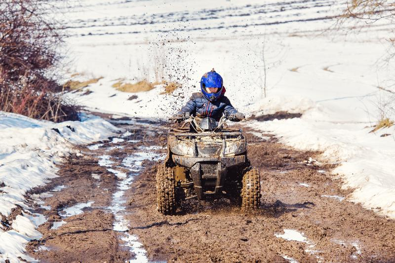 The boy is riding an ATV off-road royalty free stock photo
