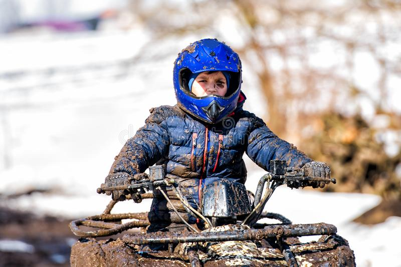 The boy is riding an ATV off-road stock image