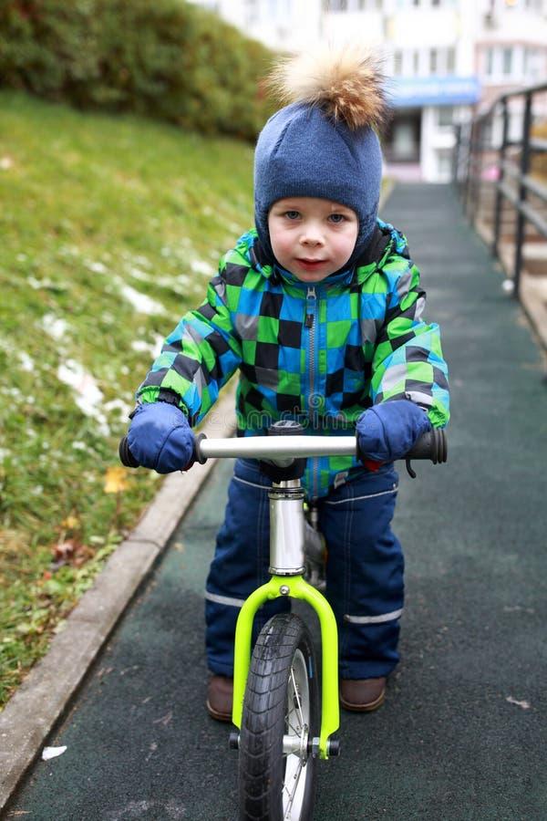 Boy riding on balance bike stock photography