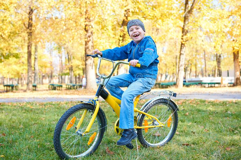 Boy riding on Bicycle in autumn Park, bright sunny day, fallen leaves on background stock photo