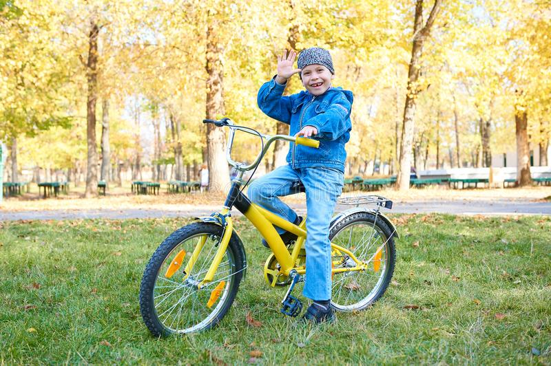 Boy riding on Bicycle in autumn Park, bright sunny day, fallen leaves on background stock photos
