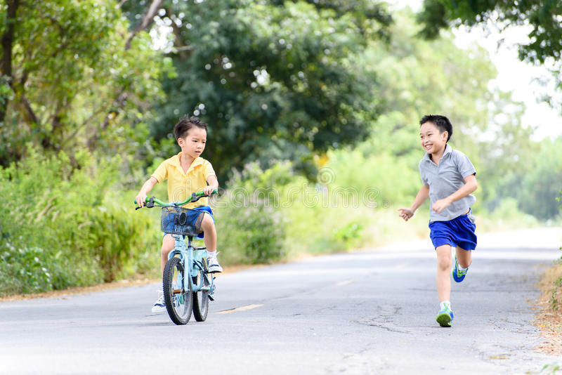 Boy riding bicycle on the road. Young Asian boy ride a blue bicycle on the old road beside the tree and grass in summer time with warm sunlight stock photo