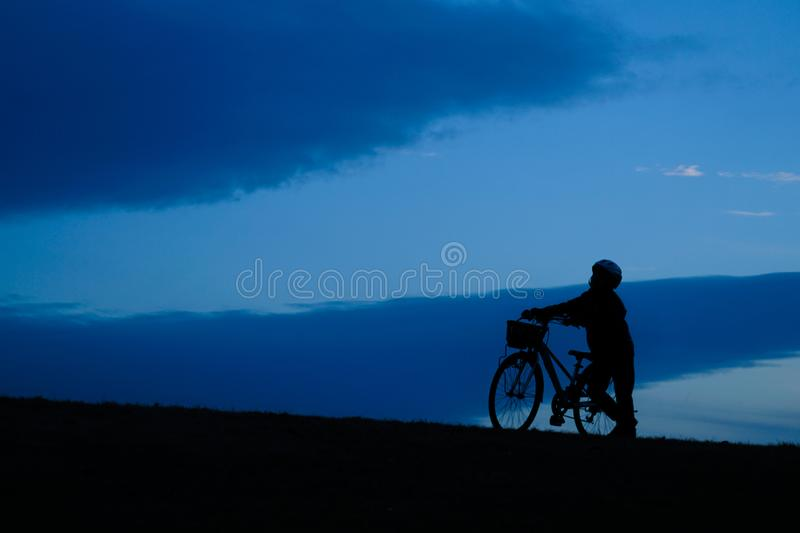 Boy riding a bicycle in the sunset of the hill. Shooting location :  Chofu, Tokyo royalty free stock image