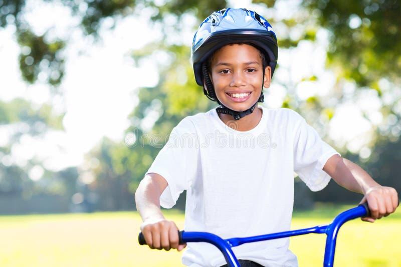 Boy riding bike. Happy young indian boy riding a bike outdoors stock photo