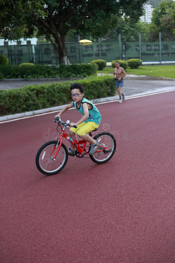 A boy riding bike on the runway stock image