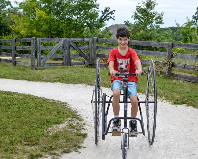 Boy Riding Old Fashioned Three Wheeled Bicycle. A young boy riding an old fashioned, three-wheeled bicycle with giant wheels stock image