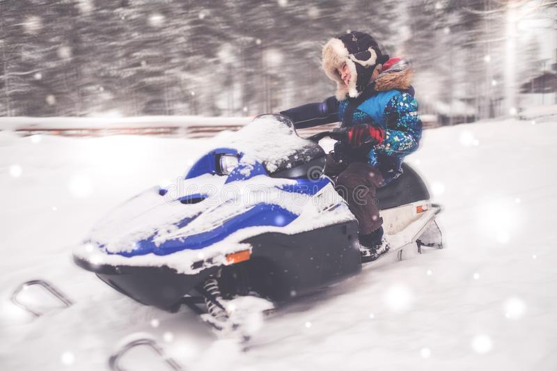 Boy driving snowmobile in a winter landscape royalty free stock photos