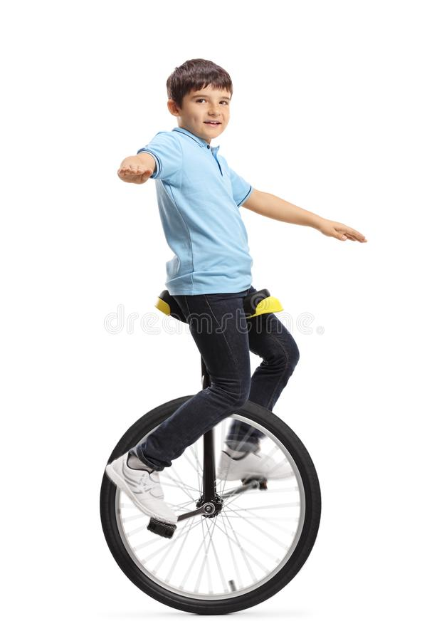 Boy riding a unicycle and looking at the camera royalty free stock photography