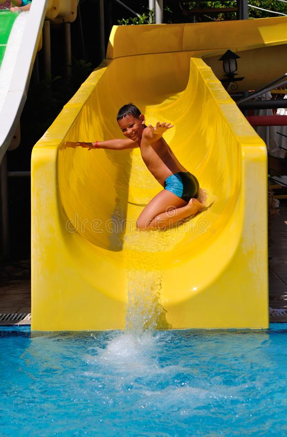 Boy riding a water slide on his knees. Boy riding in the water park on his knees stock photos