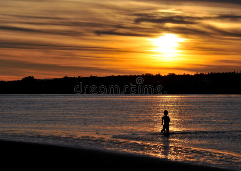 Boy in river at sunset stock image
