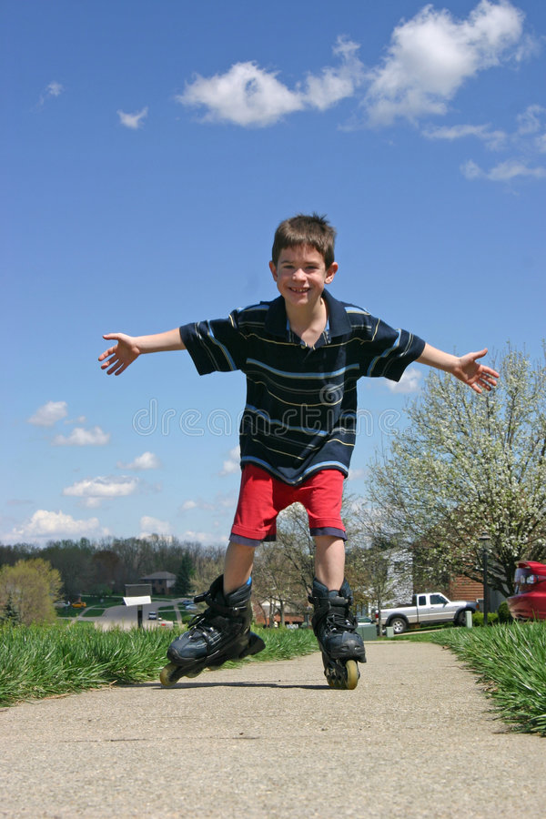 Boy Roller-Blading. With a blue sky in the background royalty free stock photos