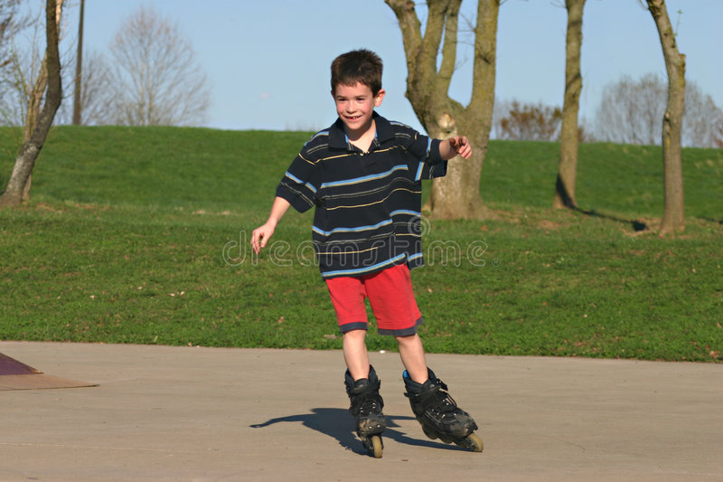 Boy Roller-Blading. Young Boy having fun Roller-Blading at the park stock photos