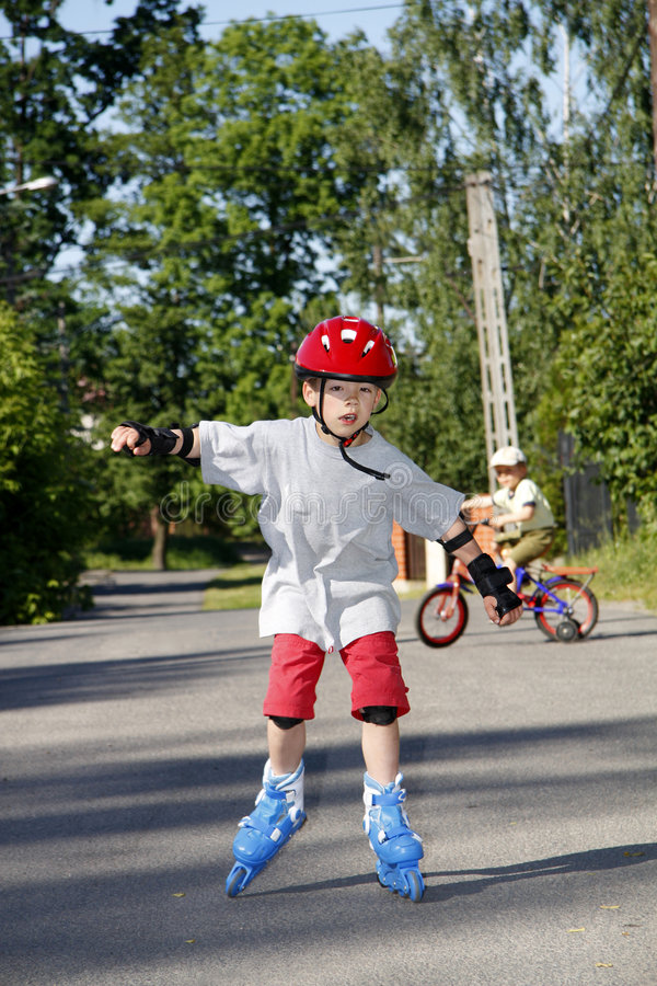 Boy roller - blading. Young boy roller - blading outdoor royalty free stock photography