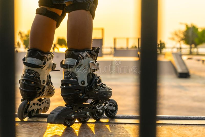 The boy rollerblading in public park with protection equipment o. N the sunset background stock image
