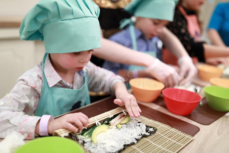 Boy rolling mat over sushi royalty free stock photos